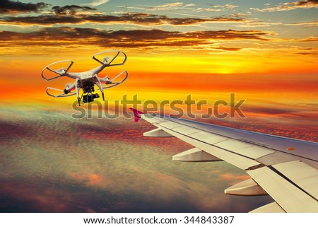 The small drone and plane on a collision course. - stock photo