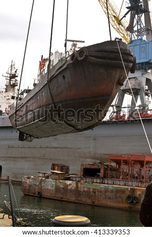 The  small  marine  vessel  rearrange   powerful  floating  crane  for  repair  of  the  ship's  hull - stock photo