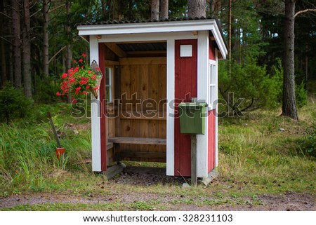 The Small wooden bus stop in the Finnish forest. - stock photo