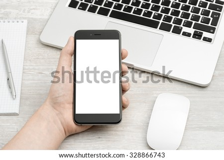 The smartphone in your hand on the table with laptop - stock photo