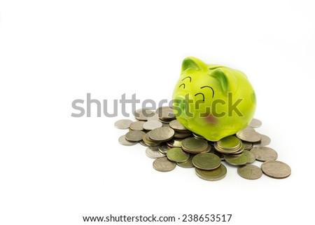 The smile green piggy bank on Thai coins. - stock photo