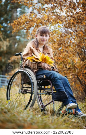 The smiling disabled girl in wheelchair in the autumn park - stock photo