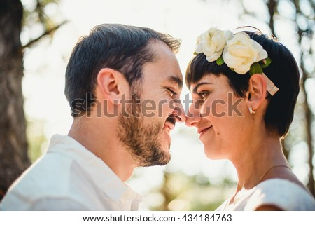 The smilling couple in love looking at each other in the forest - stock photo