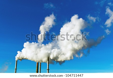 the smoking chimneys of a factory against a blue sky. white smoke rising from chimneys at - stock photo