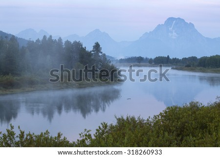 The Snake River in the mist before dawn, with Teton mountains in the background and a red glow in the sky, from Oxbow Bend, Jackson Hole, Wyoming. - stock photo
