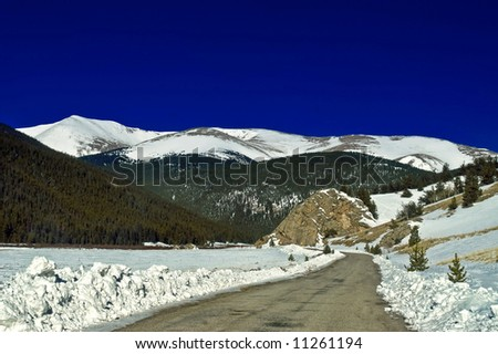 The snow covered Colorado Rocky Mountains with blue sky seem to come to life along Guanella Pass - stock photo