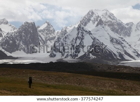 The snow mountains and alone hiker - stock photo