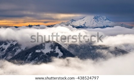 The Snowy Peak of Mount Rainier Towering Above the Clouds.