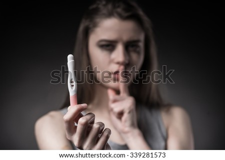 The social problem. A young pregnant woman unhappy with the test that he wants to have an abortion - stock photo