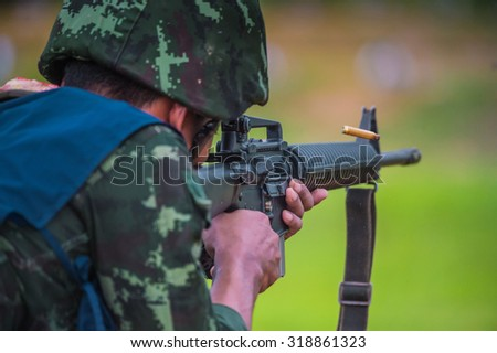 The soldiers fired M16 practice shooting firearms, ammunition, smoke, sound landscapes in forests, grasslands , behind the green .  - stock photo