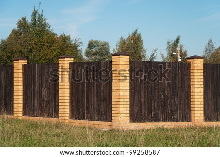 The solid wooden fence with brick pillars - stock photo
