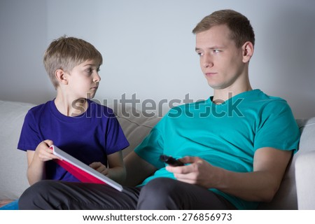 The son asks his father to help him with homework - stock photo