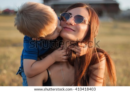 The son kisses and hugs his mom in sunglasses outdoors. Mother and her child having fun together. Little kid express the love to his young mommy.  - stock photo