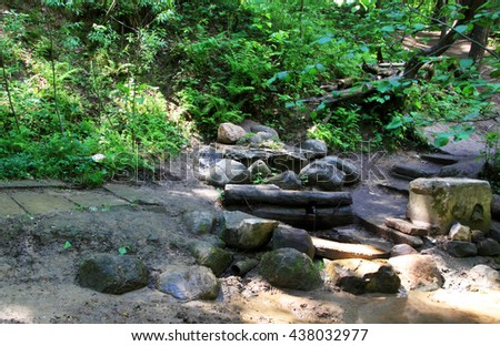 The source of the river among the rocks in the forest - stock photo