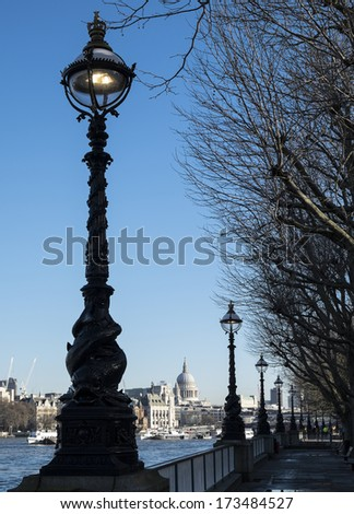 The south bank of the Thames and the old victorian lighting with St Paul's Cathedral and the London skyline in sunlight. - stock photo