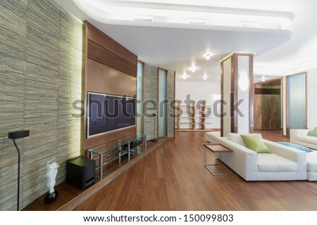 The spacious, well lit living room with a column, chairs and television set - stock photo