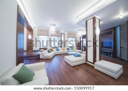 The spacious, well lit living room with a round glass table, chairs and sofa - stock photo