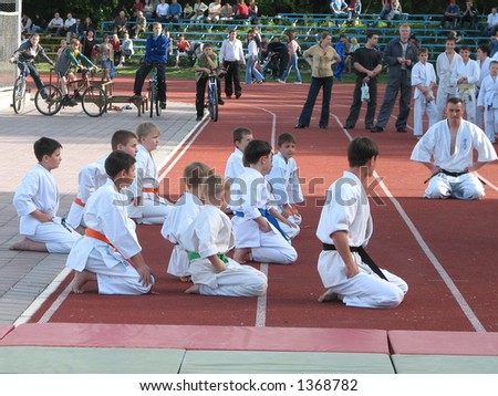 The spectators look at performance of the young sportsmen - stock photo