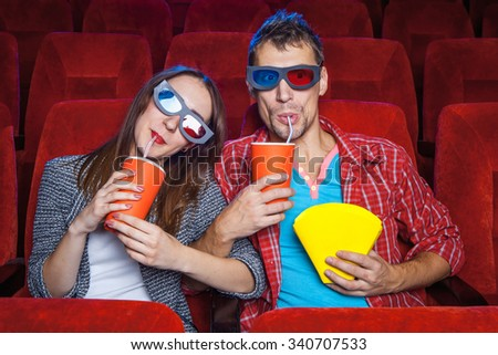 The spectators sitting in the cinema and watching movie  with cups of cola and popcorn. Concept of a variety of human emotions.  - stock photo