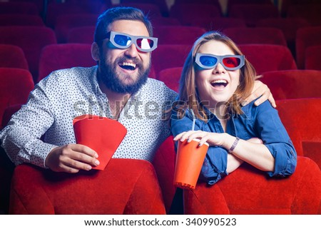 The spectators sitting in the cinema and watching movie  with cups of cola . Concept of a variety of human emotions.  - stock photo