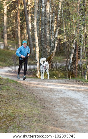The sports woman with a dog run  in park - stock photo