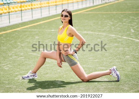 The sportswoman in training sits and stretches - stock photo