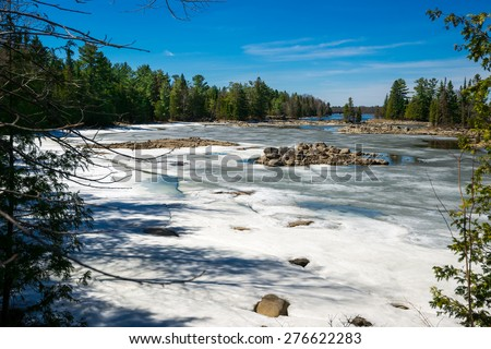The spring thaw melts the snow covering a lake inlet in the wilderness of Ontario, Canada. - stock photo