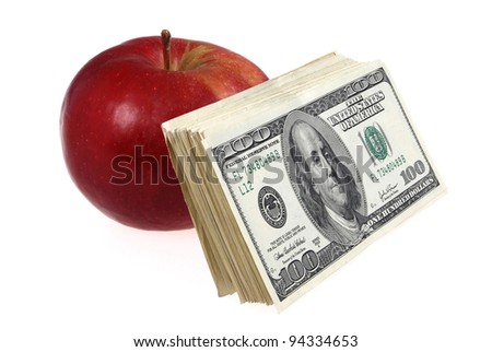 The stack of dollars lays near an apple. On grey background. - stock photo