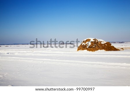 The stack of straw covered with snow. A winter season - stock photo