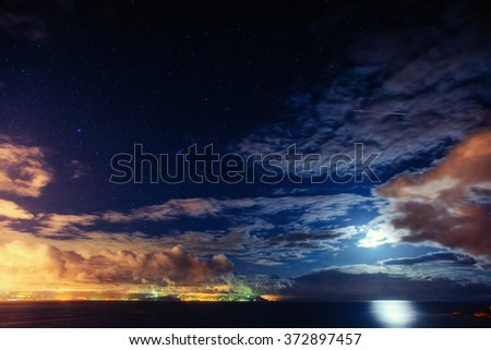 The starry sky above rocky mountains. Fantastic lighting city that appears in the sea - stock photo
