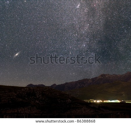The stars of the Milky Way over an Alpine village. Andromeda galaxy to the left. - stock photo