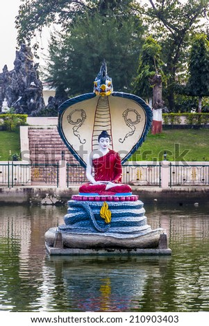 The statue depicts the Buddha, protected by the king of the serpents. It is situated near the famous Mahabodhi temple at Bodhgaya, India. - stock photo