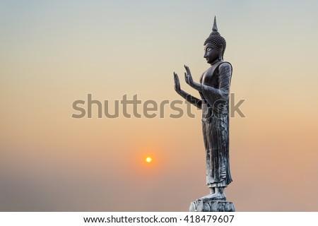 The Statue of Buddha on sunset sky background. - stock photo