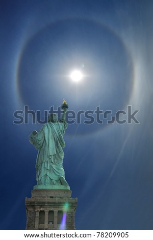 The Statue of Liberty on its back facing a 22° halo in the sky over New York City on March 30, 2011. - stock photo