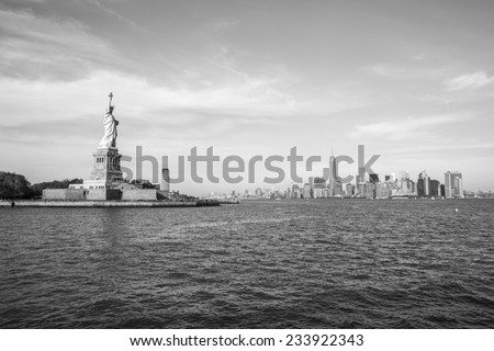 The Statue of Liberty with the Manhattan skyline in the background, in New York, USA. (black and white) - stock photo