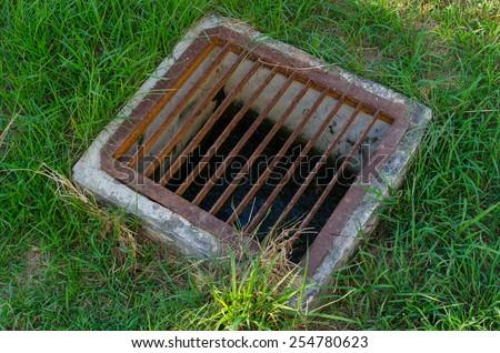 The steel floor drain, running water from the meadow in garden - stock photo