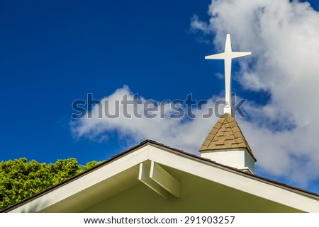 The steeple and cross on the roof of a small chapel - stock photo