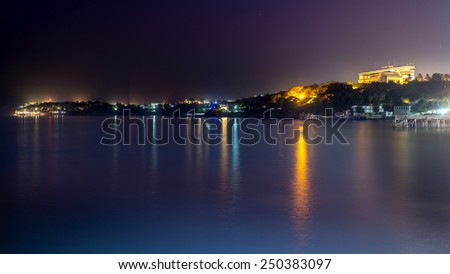 The still waters of the Atlantic ocean reflecting the colourful lights along the shores of downtown Dakar - stock photo