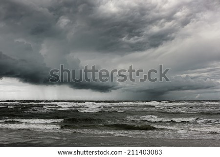 The stormy rain is approaching. The approaching shower over the North Sea. Extremely windy on the shore. - stock photo