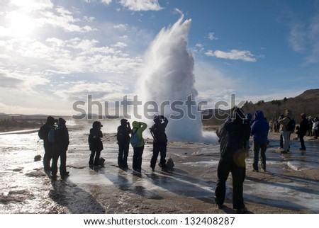 The Strokkur geyser in Iceland is erupting while tourists are looking - stock photo