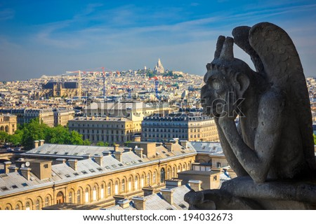 The Stryge (most famous of the Chimeres) looking toward Basilica of the Sacred Heart of Jesus at Notre Dame Cathedral in Paris - stock photo