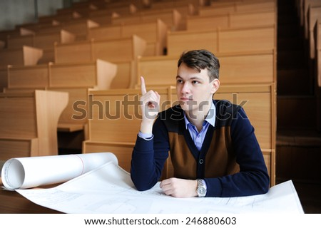 The student in large audience, sitting at a school desk, prepares for examination - stock photo