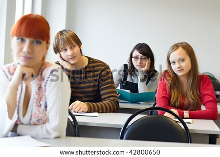 The students on employment sits at a table indoors - stock photo