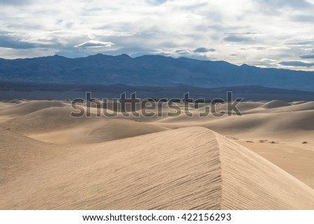 The stunning backdrop of the dramatic snow-covered mountains behind the surreal mesquite sand dunes in Death Valley National Park - stock photo