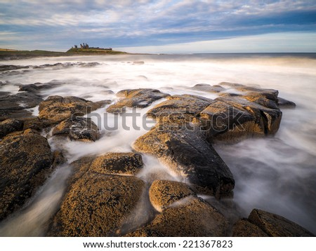 The stunningly rugged coastline of Holy Island in Northumberland is protected by Lindisfarne Castle on a beautiful winters morning. - stock photo