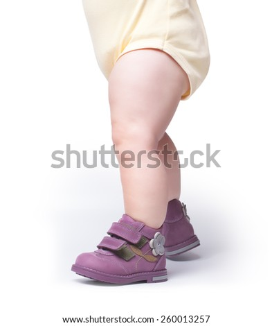the stylish baby goes in boots. isolated on white background - stock photo