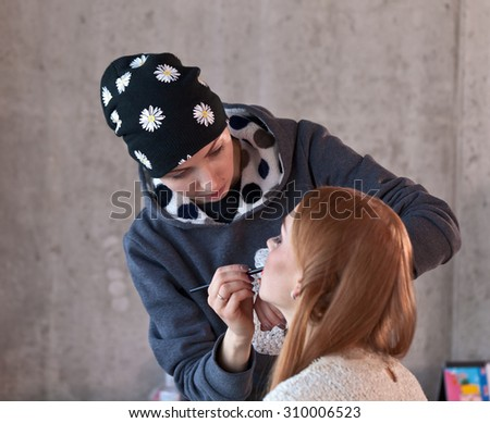 The stylist does a make-up for photosession - stock photo