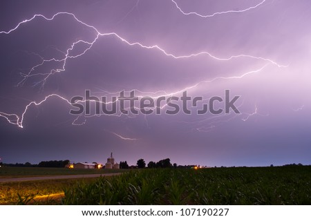 The summer drought is broken up by a rare thunderstorm. The lightning is a flash of optimism to the farming community. - stock photo