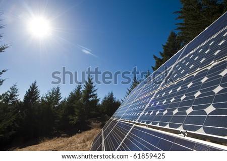 The sun beams down on multiple solar panels along the northern California coast. - stock photo