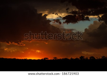 The sun dips below the horizon over the African wilderness after a violent thunderstorm. - stock photo